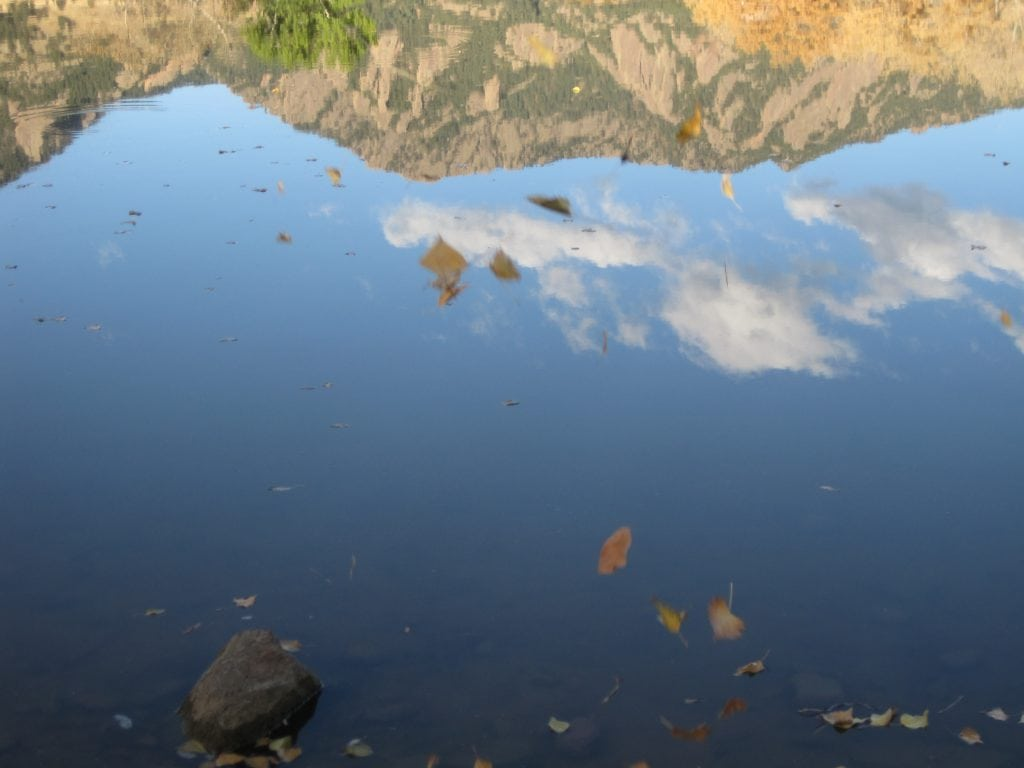mountains reflected in lake with leaves